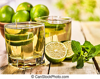 On wooden boards is glass with green mohito drink. - Country...