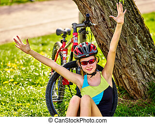 Bikes child wearing helmet. Girl in cycling sitting near bicycle.