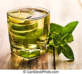 Glass with green transparent lime drink and mint. - Alcohol...