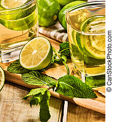Glasses with green transparent lime drink and mint napkin. -...
