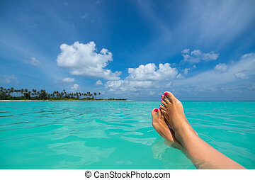 Close-up of female foot in the blue water on the tropical...