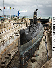 old submarine surfaced - shipyard in the port, with old...