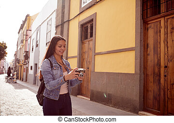 Pretty young smiling girl with her camera