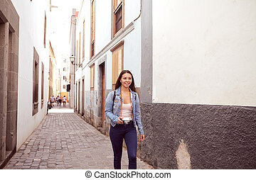Pretty young lady walking hurriedly with backpack - Pretty...