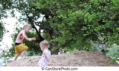 Children jumping into the sandbox - Two girls playing in a...