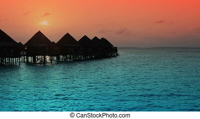 houses over the transparent quiet sea water on a sunset ,