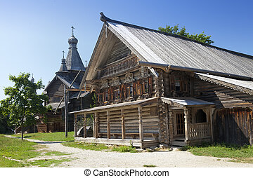 Ancient wooden church and wooden log hut on a forest glade....