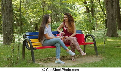 Two beautiful young women chatting in the park