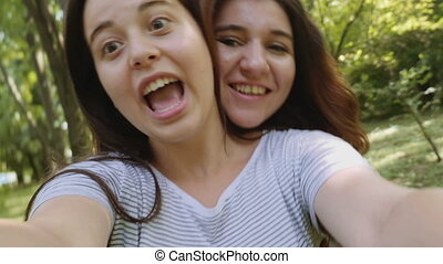 Beautiful young women taking selfie in the park