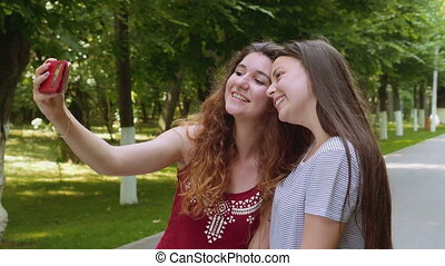 Happy friends taking selfie with the smartphone in the park