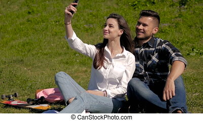Young Couple Make Selfi Sitting on Grass In a Park