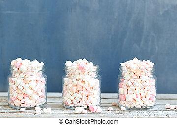 Three glass jars filled to brim marshmallow - Three glass...