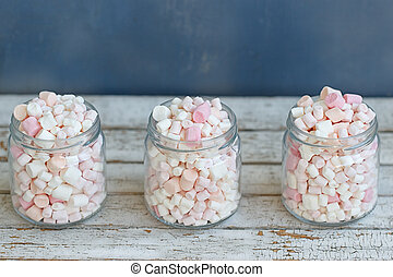 Three glass jars filled to brim marshmallow - Three glass...