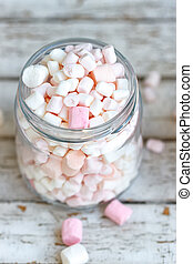 One glass jar filled up with marshmallow on white wooden...