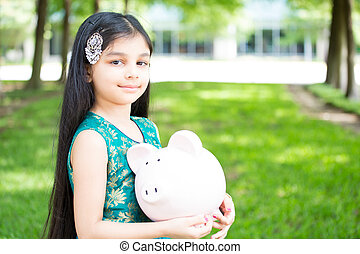 Children saving - Closeup portrait, young girl holding piggy...