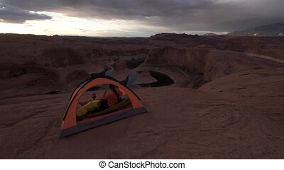 Camping Breakfast Young Woman enjoying a cookie looking at...