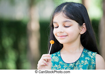 Girl enjoying lolly - Closeup portrait, young girl enjoying...