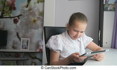 Cute little girl uses a digital tablet computer - Cute...