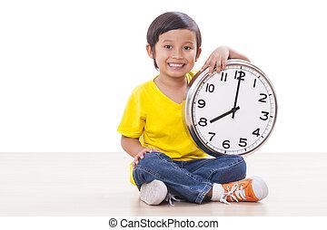 Cute boy is holding big clock