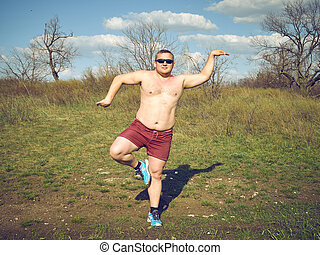 Fat man doing yoga outdoors in nature
