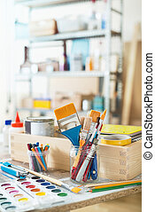 Paint brushes and crafting supplies on the table in a...