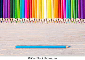 Color pencils on wooden background with single blue pencil