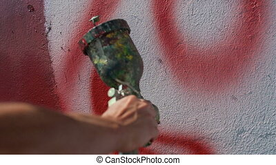artist paints on the wall with air gun