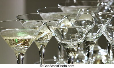 Pouring champagne into a glasses standing on table at the bar in festive evening