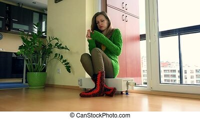 Young Frozen Woman Adjusting Thermostat On Radiator At Home...