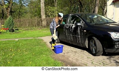 woman wash black car with soapy sponge.