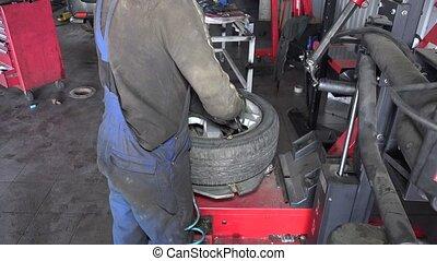 mechanic inflating tire on wheel in workshop. Seasonal tire...
