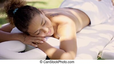 Woman on massage table at outdoor spa - Top side view on...