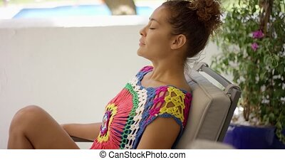 Single woman in colorful knit top sitting in chair - Profile...