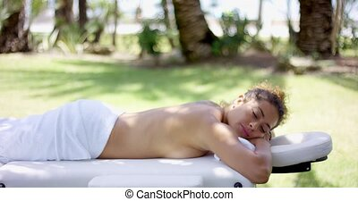 Woman in towel laying on massage table at outdoor spa with...
