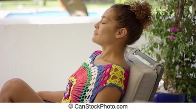 Smiling woman in colorful top sitting in chair - Smiling...
