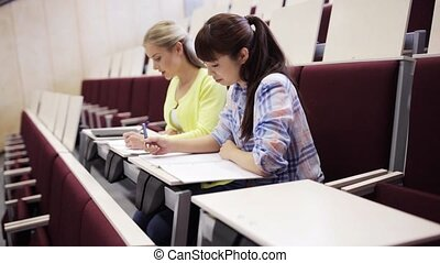 student girls with notebooks in lecture hall