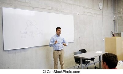 teacher at white board and students on lecture - education,...