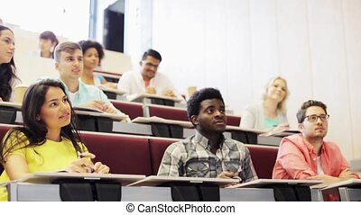 group of students talking to teacher at lecture - education,...