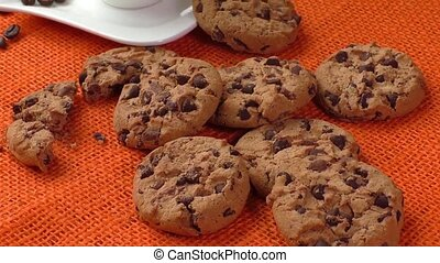 Chocolate chip cookies and cup of coffee shot on jute...