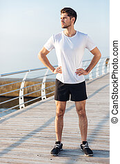 Sportsman standing on wooden terrace in the morning