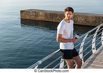 Sportsman standing and drinking water on pier - Serious...