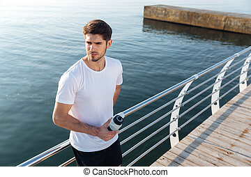 Sportsman standing near the sea and drinking water -...