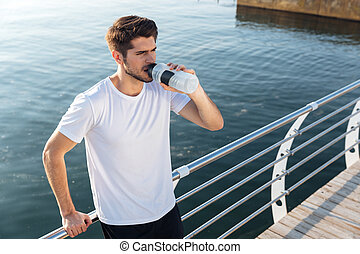 Sportsman standing on wooden terrace near sea and drinking...