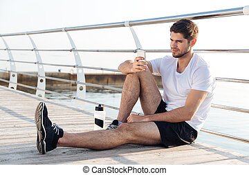 Relaxed young sportsman athlete resting and using mobile...