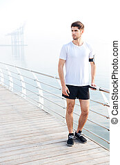 Sportsman standing on pier near the sea - Handsome