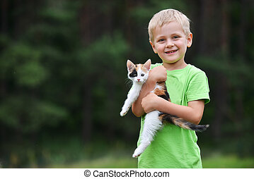boy with motley cat - boy playing with motley cat on green...