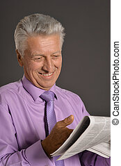 Senior man reading newspaper isolated on gray