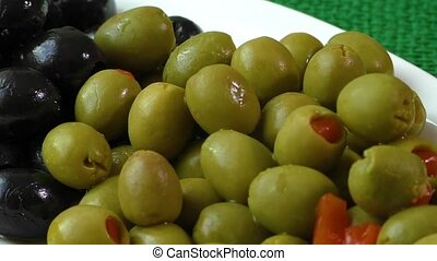 Green and black olives on a white plate