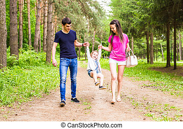 Happy young family spending time together outside in green nature.