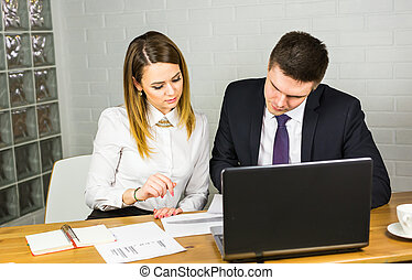 young business colleagues discussing work on a laptop computer in co-working space, corporate businesspeople